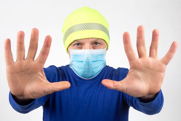Ritratto di un uomo in una mascherina medica con le mani alzate. mani pulite e quarantena