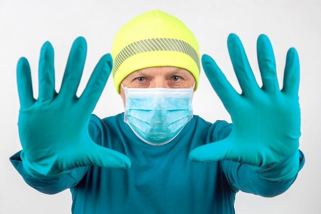 Ritratto di un uomo in una mascherina medica con le mani alzate in guanti protettivi. mani pulite e quarantena