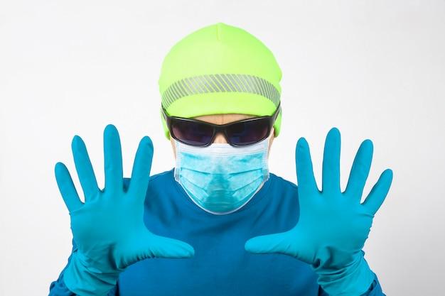 Ritratto di un uomo in una mascherina medica con le mani alzate in guanti protettivi