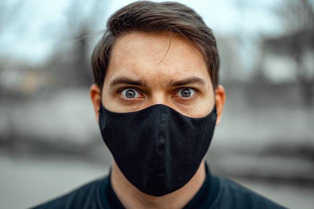 Ritratto di uomo in maschera medica. il giovane sta su sfondo chiaro e guardando la fotocamera.