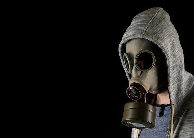 Ritratto di un uomo in una vecchia maschera antigas militare su sfondo nero. copia spazio