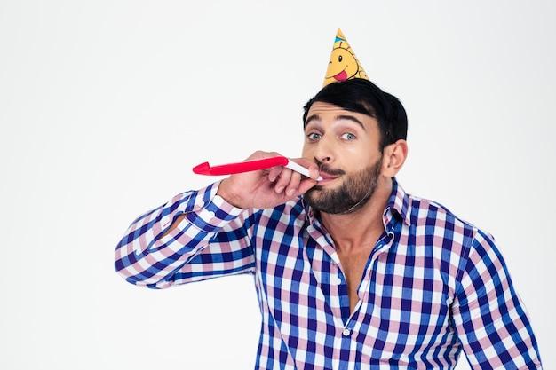 Ritratto di un uomo in cappello del partito che soffia nel fischio isolato su un muro bianco