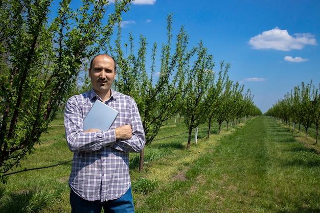 Ritratto di proprietario di piantagione uomo con tablet in piedi nel suo frutteto.