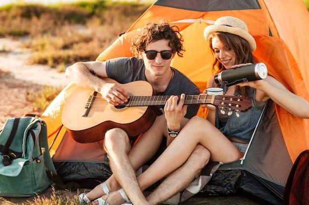 Ritratto di un uomo che suona la chitarra per la sua ragazza in campeggio sulla spiaggia