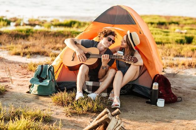 Ritratto di un uomo che suona la chitarra per la sua ragazza seduta alla tenda da campeggio