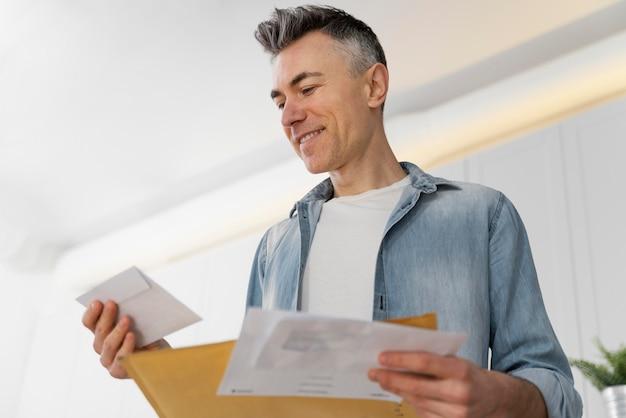 Uomo del ritratto che legge la posta