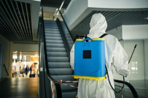 Ritratto di un uomo in una tuta disinfettante che tiene spray vicino alla scala mobile in un centro commerciale vuoto. un volontario che ripulisce i luoghi pubblici per prevenire il covid-19. concetto di consapevolezza della salute.