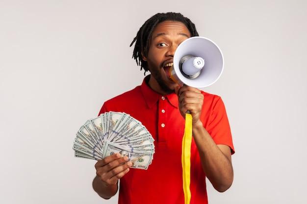 Ritratto dell'uomo che grida nel megafono che tiene fan di dollari, bonus vacanze e promozioni.
