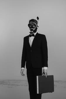Ritratto di un uomo una spia di agente segreto in un vestito e una maschera da sub con una valigia in mano in piedi
