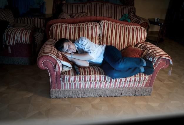 Ritratto di uomo che dorme sul divano di notte vicino alla tv