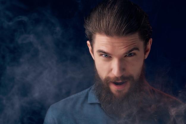 Ritratto di un uomo che fuma nicotina moda stile di vita isolato sfondo