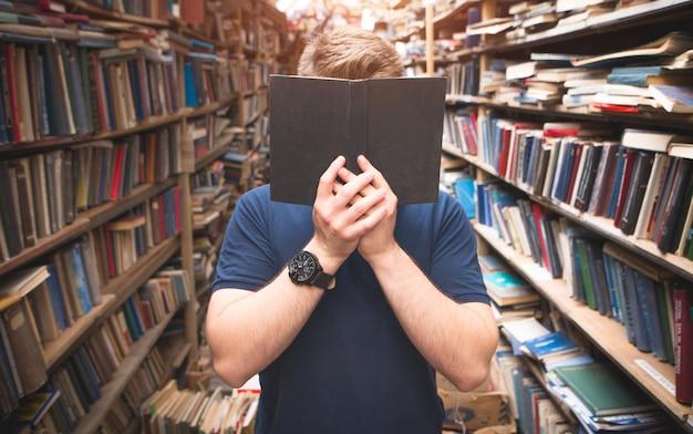 Il ritratto di un uomo in piedi nella biblioteca si copre il volto con un libro nero aperto