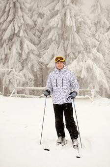 Ritratto di un uomo in piedi con gli sci e in posa contro montagne innevate e foreste