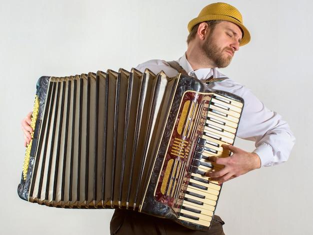 Ritratto di un uomo in cappello di paglia che gioca sulla fisarmonica