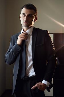Ritratto di un uomo in giacca e cravatta vicino alla finestra. lo sposo si sta preparando per la cerimonia nuziale