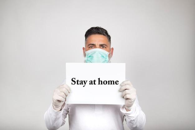 Il ritratto dell'uomo nella maschera chirurgica che tiene un segno bianco con la frase resta a casa su fondo bianco. prevenzione del coronavirus