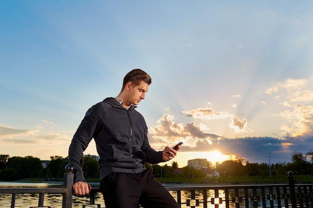 Ritratto di un uomo che si prende una pausa dalla corsaparlando al telefonojogging