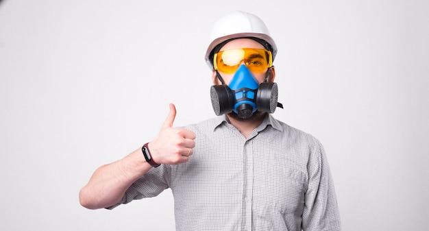 Ritratto di uomo con respiratore e casco da portare e mostrando il pollice sul gesto