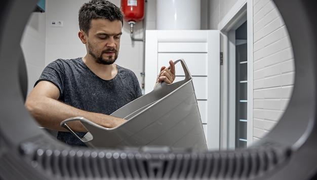 Ritratto di un uomo, vista dalla lavatrice, che carica e lava la biancheria sporca.