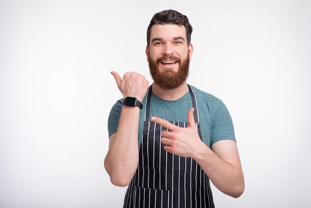 Il ritratto di un uomo che indossa un grembiule da cucina sul muro bianco sta indicando il suo smartwatch