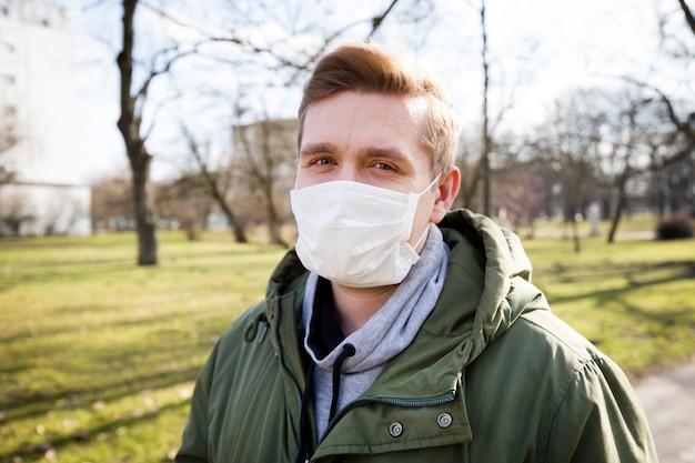 Ritratto di un uomo che indossa la maschera medica su un bacground parco pubblico della città. pandemia di coronavirus. concetto di inquinamento atmosferico, focolaio di polmonite, smog o epidemia