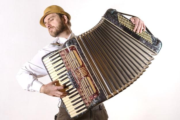 Ritratto di un uomo che indossa un cappello di paglia e una camicia bianca che suona emotivamente la fisarmonica