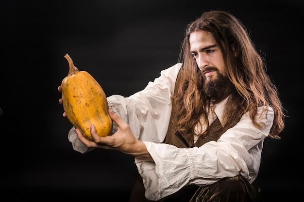 Ritratto di un uomo con barba e capelli lunghi che indossa un costume da pirata medievale su un muro nero, un pirata che tiene una zucca matura