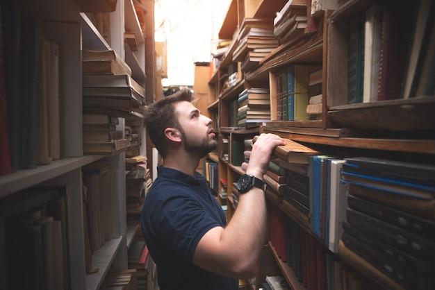 Ritratto di un uomo con la barba guardando uno scaffale e scegliendo un libro
