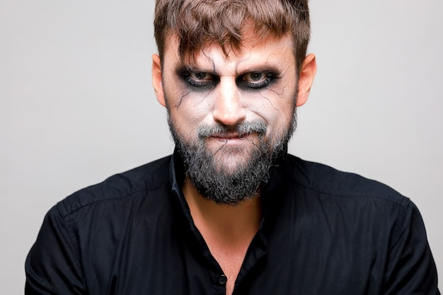 Ritratto di un uomo con la barba e uno sguardo minaccioso con il trucco in stile non morto il giorno di ognissanti il 31 ottobre