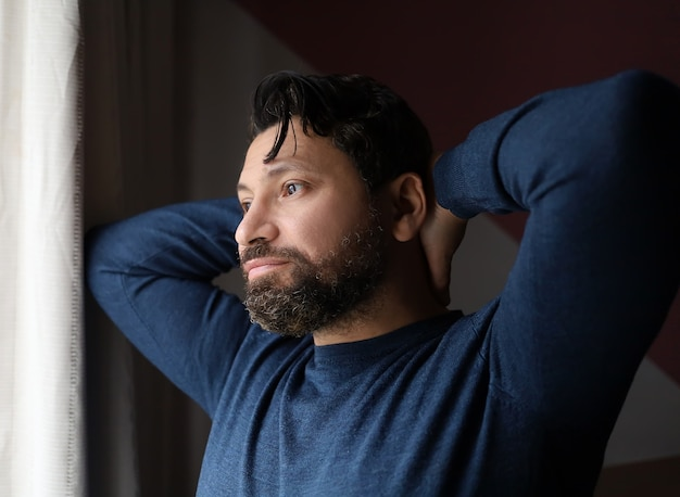 Ritratto di un uomo con la barba che si allunga e guarda la finestra, mattina a casa, inizio giornata
