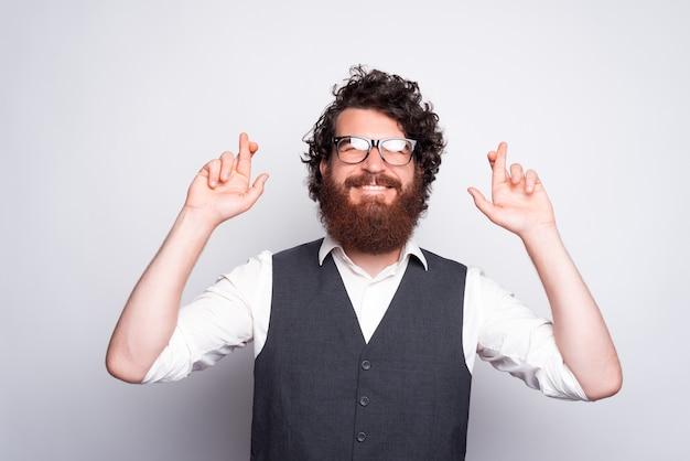 Ritratto di uomo con la barba che indossa tuta e dita incrociate e che esprime un desiderio
