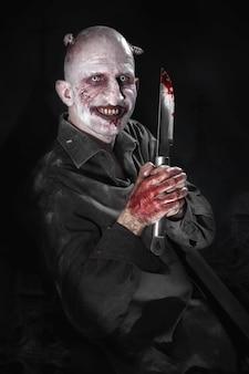 Ritratto di un uomo con un coltello insanguinato travestito da zombie su sfondo nero.