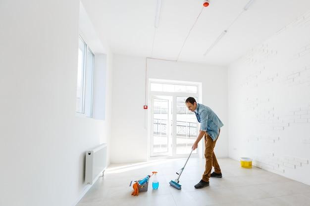 Ritratto di uomo con attrezzatura per la pulizia che pulisce la casa