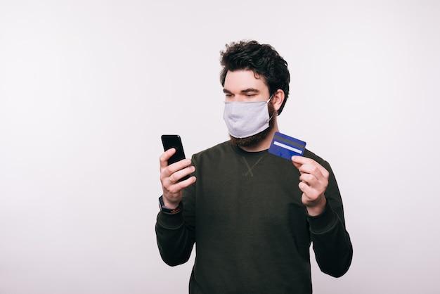 Ritratto di uomo con maschera facciale utilizzando il suo smartphone e la carta di credito