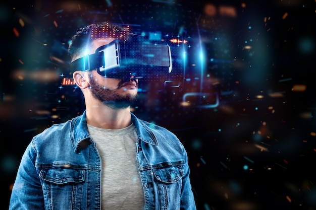 Ritratto di un uomo con gli occhiali della realtà virtuale, vr, interagisce con uno schermo virtuale.