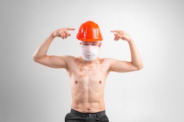 Ritratto di uomo con la faccia ferita e la testa bendata che mostra con le dita al casco protettivo sulla sua testa