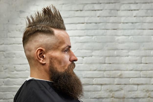 Ritratto di un uomo con un mohawk e la barba in una poltrona da barbiere contro un muro di mattoni. primo piano, sfondo di mattoni, copia dello spazio.