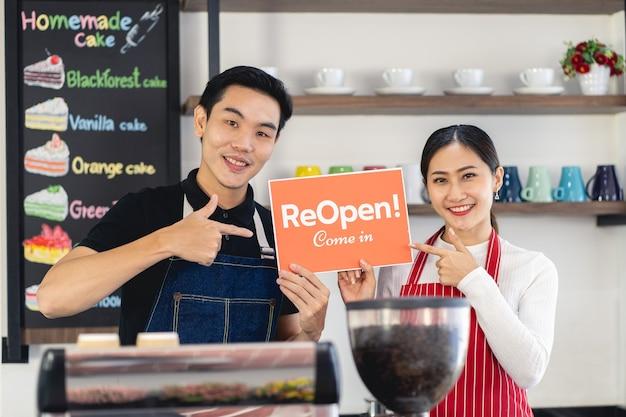 Ritratto di uomo e donna cameriera in piedi al cancello della sua caffetteria con mostrando cartello chiuso showing