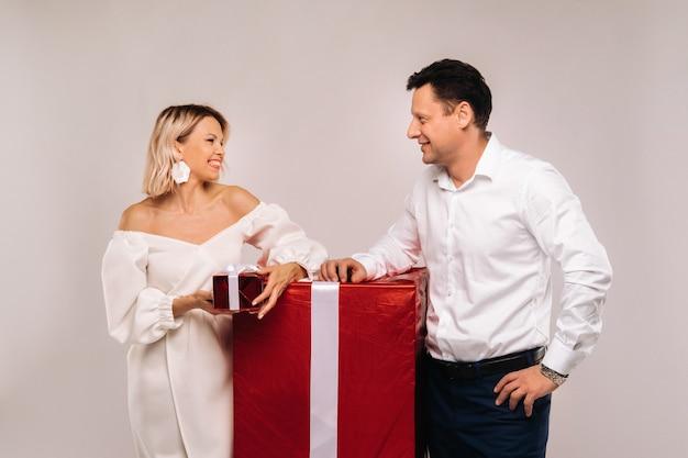 Ritratto di un uomo e di una donna con un grande regalo su fondo beige