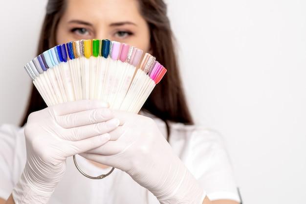 Ritratto del maestro di manicure con la tavolozza del campione di unghie su bianco