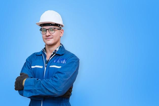Il ritratto dell'operaio manuale è in piedi con fiducia davanti a sfondo blu