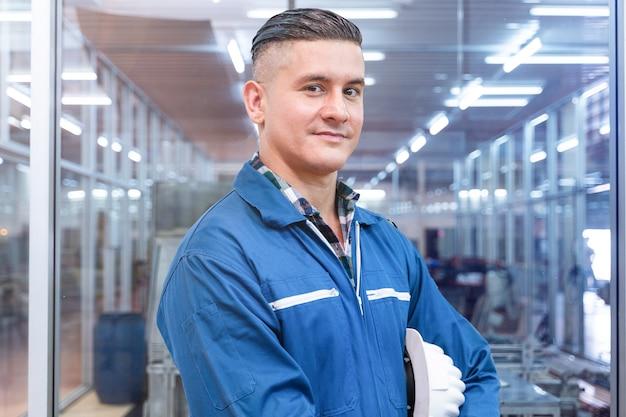 Il ritratto dell'operaio manuale è in piedi con fiducia con il riflesso verde della suite di lavoro blu