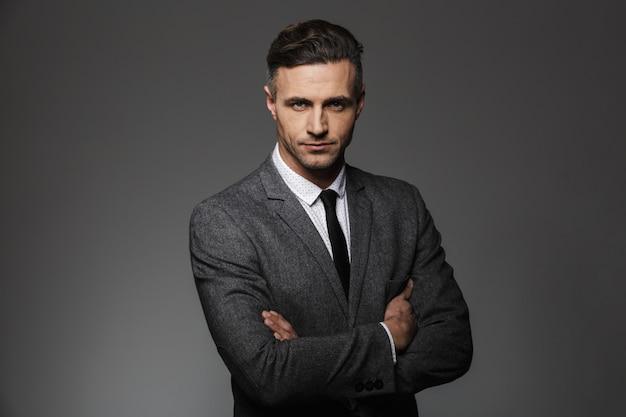 Ritratto di uomo d'affari che indossa tailleur in posa con sguardo serio mantenendo le braccia conserte, isolato su muro grigio