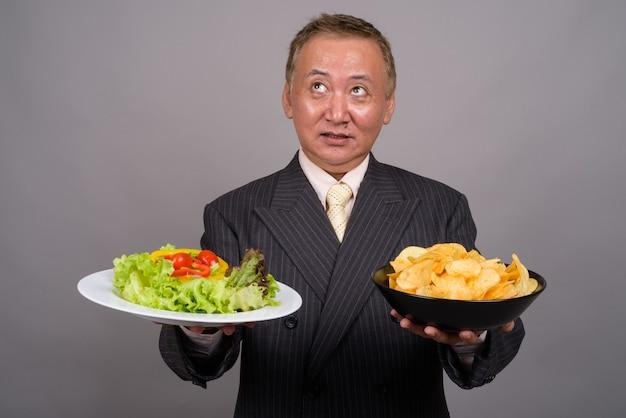 Ritratto di maturo uomo d'affari asiatico contro il muro grigio
