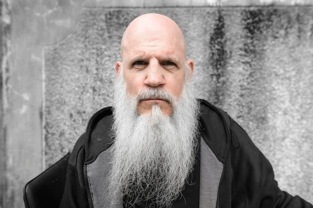 Ritratto di uomo calvo maturo con una lunga barba grigia contro il muro di cemento grunge all'aperto