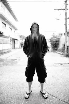 Ritratto di uomo calvo maturo con una lunga barba grigia nelle strade all'aperto in bianco e nero