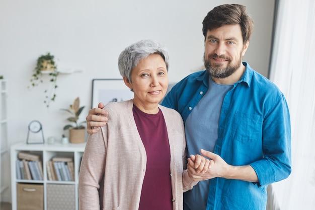 Ritratto di uomo barbuto maturo che si prende cura della donna senior che la abbraccia e le tiene la mano in piedi nel soggiorno e sorridente