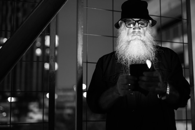Ritratto di uomo barbuto maturo guardando sospettoso al buio scala