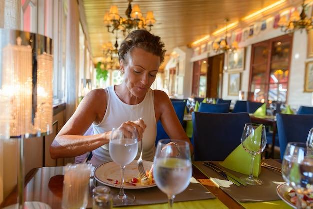 Ritratto di bella donna scandinava matura con i capelli corti al ristorante al chiuso