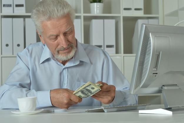Ritratto di un uomo d'affari maturo in ufficio con soldi